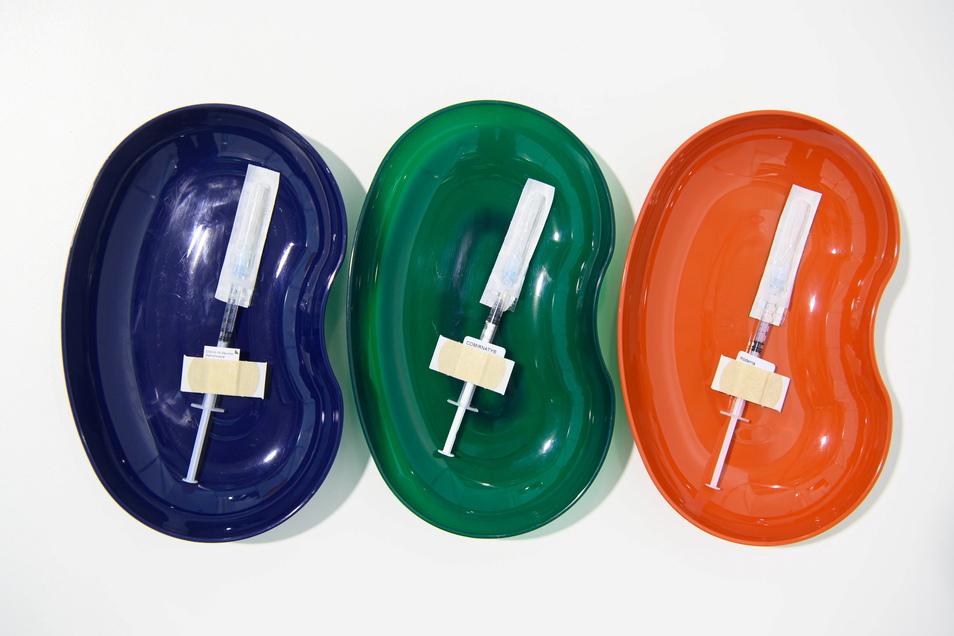 Nach Farben sortiert: Spritzen mit dem Astrazeneca-Wirkstoff, dem des Herstellers Biontech/Pfizer und von Moderna (v.l.) liegen für die Impfung gegen Corona vorbereitet in Schalen.