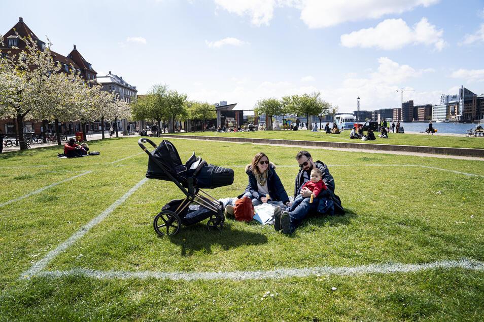 Eine Familie genießt die Sonne in Kopenhagen. Markierte Flächen auf dem Grasland helfen den Menschen, Abstand voneinander zu halten, wobei etwa 40 Quadratmeter Fläche für maximal 10 Personen markiert sind.