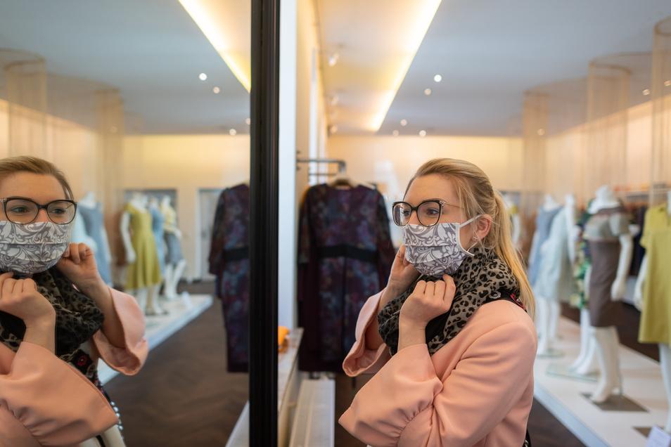 Modisches Accessoire: Eine Kundin probiert in einer Boutique einen Mundschutz an.