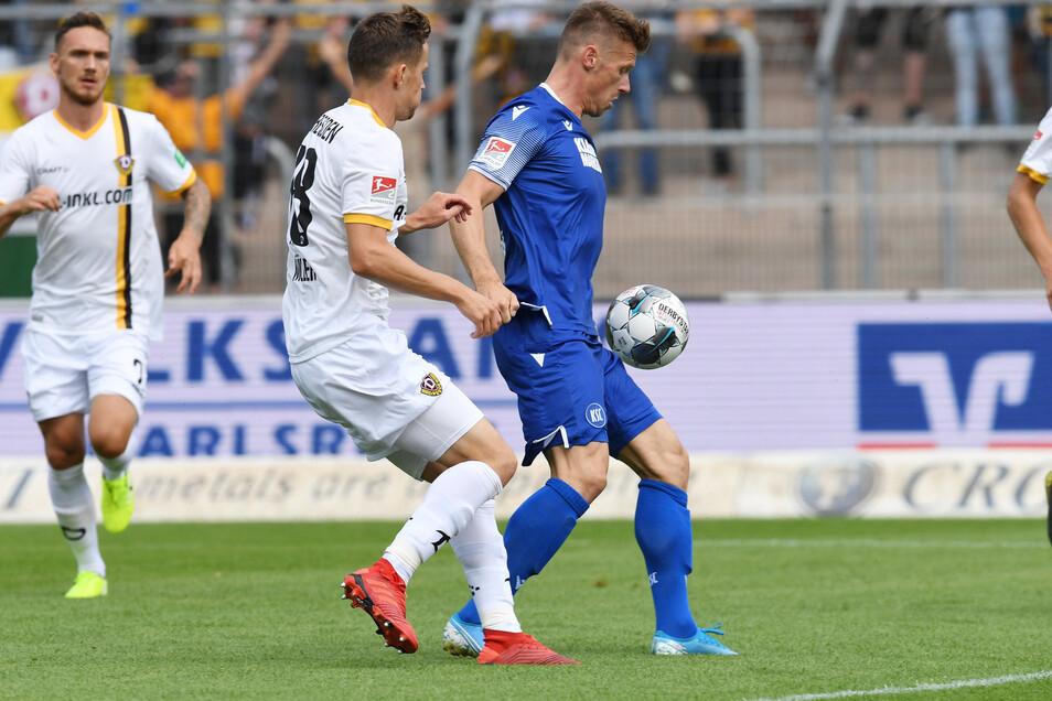 Der Karlsruher Marvin Pourie (r) und der Dresdner Jannik Müller kämpfen um den Ball.