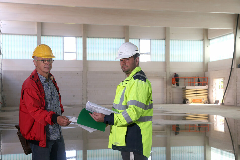 Steffen Uschner (l.) und Denny Wolf in der neuen Turnhalle. Gerade wird hier an der Verglasung gearbeitet.