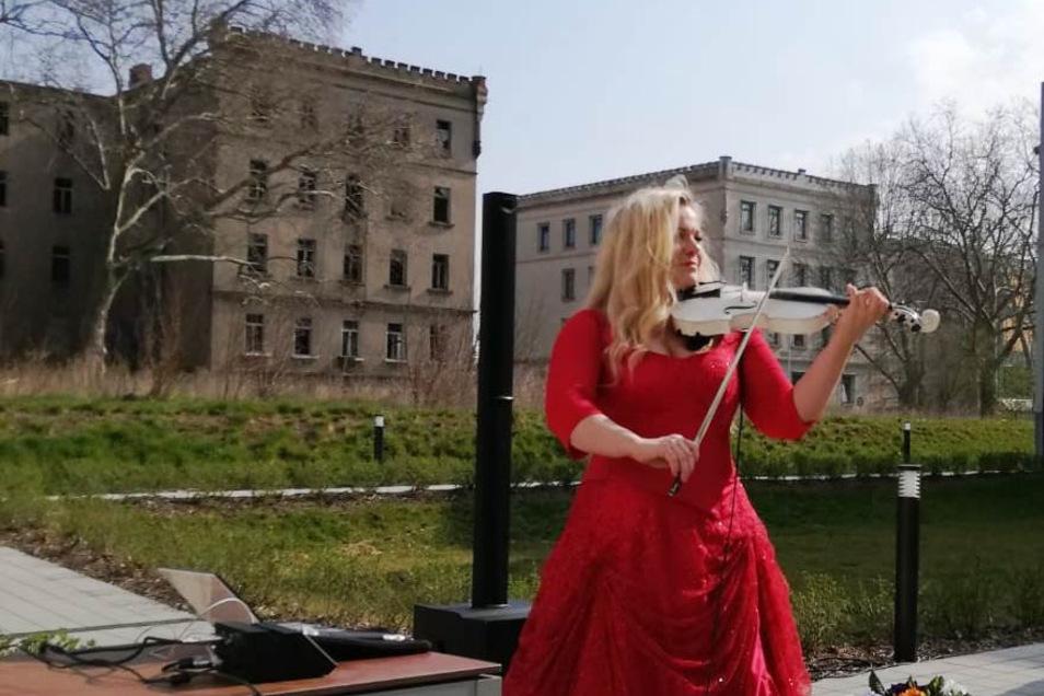 Die Geigerin Katrin Wettin bei ihrem Konzert im Innenhof des Riesaer Azurit-Seniorenzentrums. Im Hintergrund das Landratsamt (r.) und die brachliegende frühere Kaserne.