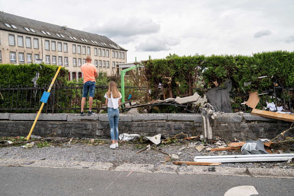 Menschen betrachten die Schäden durch den lokalen Wirbelsturm.