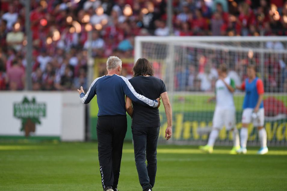 Schiedlich friedlich: Nach dem 1:1 zwischen Freiburg und Augsburg laufen SC-Trainer Christian Streich (l) und FC-Coach Martin Schmidt Arm in Arm über den Rasen.