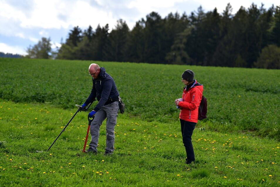 Ronny Schott schwingt den Metalldetektor vorsichtig über der Erdoberfläche. Redakteurin Gabriele Fleischer beobachtet ihn dabei.