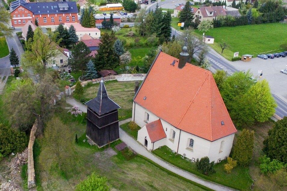 Dieses Luftbild macht die Besonderheit von Lauta-Dorf deutlich. Der hölzerne Turm, der frei neben der Kirche steht, beinhaltet die Kirchenglocken.