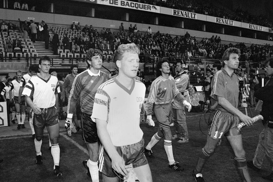 Angeführt von Kapitän Matthias Sammer (M, vorn) betritt die DDR-Fußballnationalmannschaft mit Torhüter Jens Schmidt (dahinter) und Verteidiger Andreas Wagenhaus (l., damals Dynamo Dresden) das Feld des Brüsseler Constant-Vandenstock-Stadions.