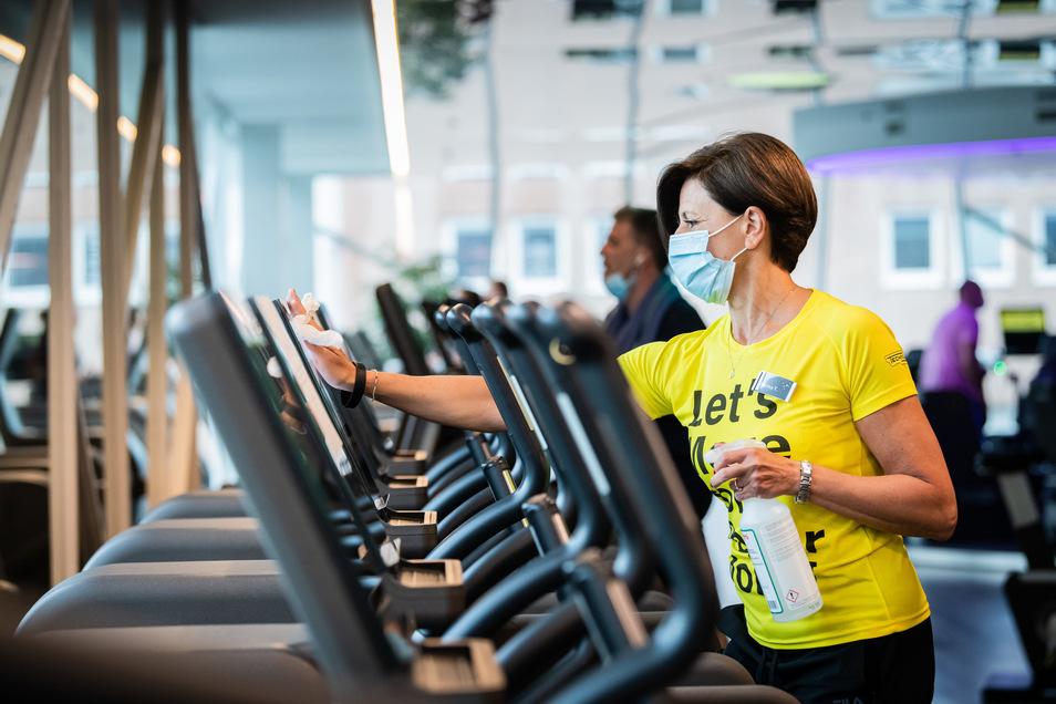 Eine Beschäftigte mit Atemschutz desinfiziert ein Laufband im Fitnessstudio.