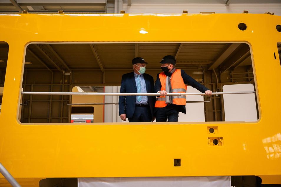 Carsten Liebig, Leiter des Bombardier Werkes Görlitz, und Ministerpräsident Michael Kretschmer (rechts) fachsimpeln im Rohbau der neuen Straßenbahn für Dresden.
