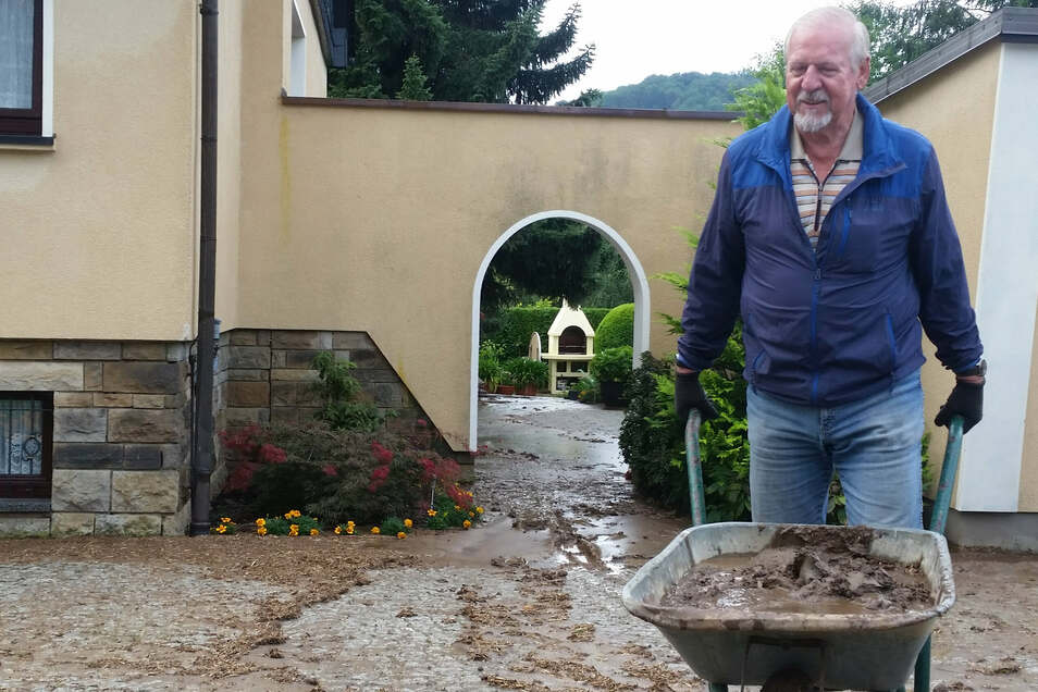 Großreinemachen nach der Überflutung am Montagmorgen: Gernot Fünfstück karrt Schlamm von seinem Grundstück am Langen Garten in Oberoderwitz.