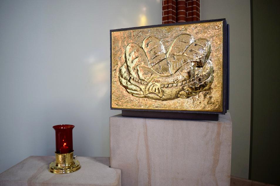 Seit der Sanierung der katholischen Kirche beherbergt dieser neue Tabernakel die gewandelten Hostien – das Zentrum der Kirche. Das Motiv hat ein Gemeindemitglied entworfen. Daneben steht das Ewige Licht.