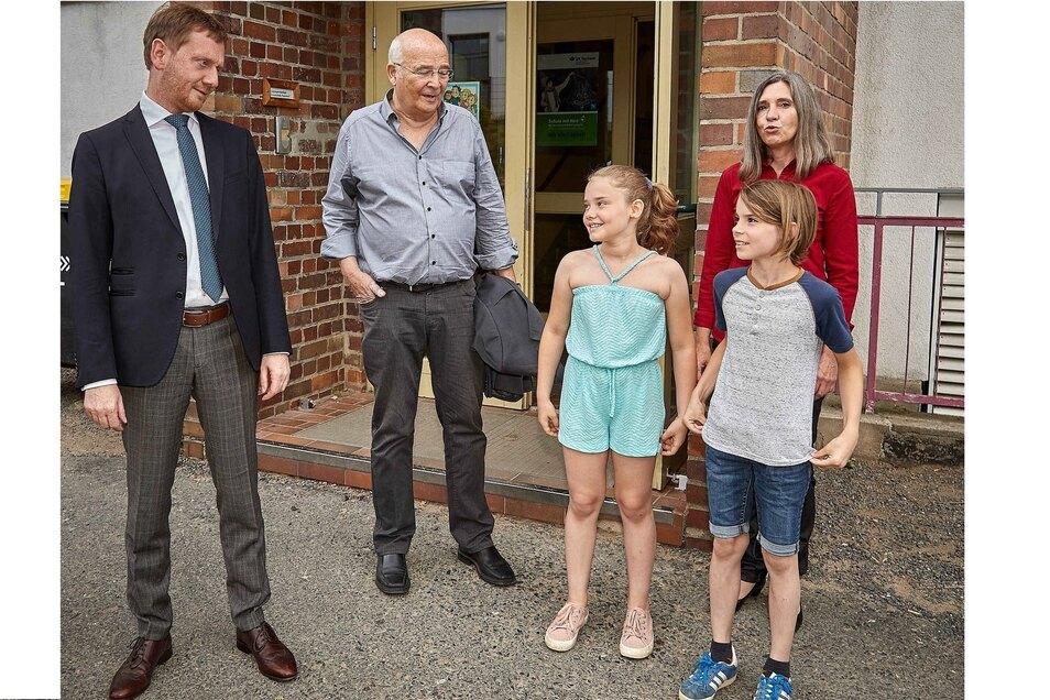 Michael Kretschmer (l.) im Gespräch mit Bürgermeister Heiko Eggert, den Schülern Katharina und  Theodor sowie Schulleiterin Kerstin Schulze.