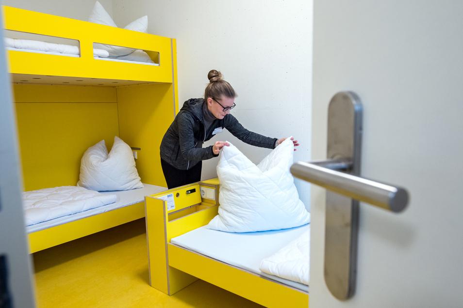 Eine Mitarbeiterin der neuen Jugendherberge richtet in einem Gästezimmer des modernen Hauses die Betten.
