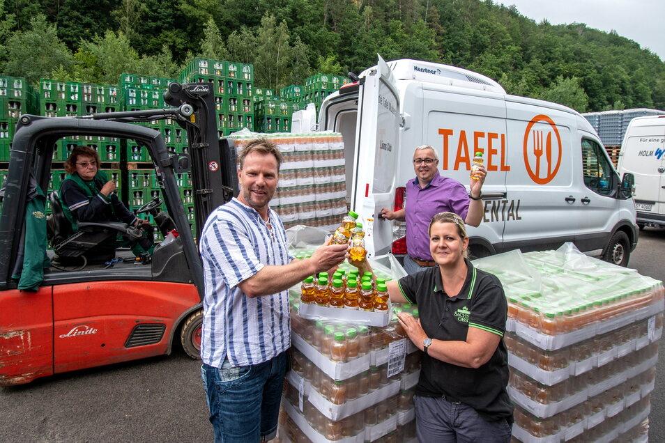 Sven Wittenberg, Projektleiter der Tafel Muldental, und Sandy Ronniger vom Marketing der Obstland AG stoßen mit Apfelsaft an. Der neue Geschäftsführer der Kelterei Sachsenobst Marcel übergibt der Tafel 4.000 Flaschen Saft.