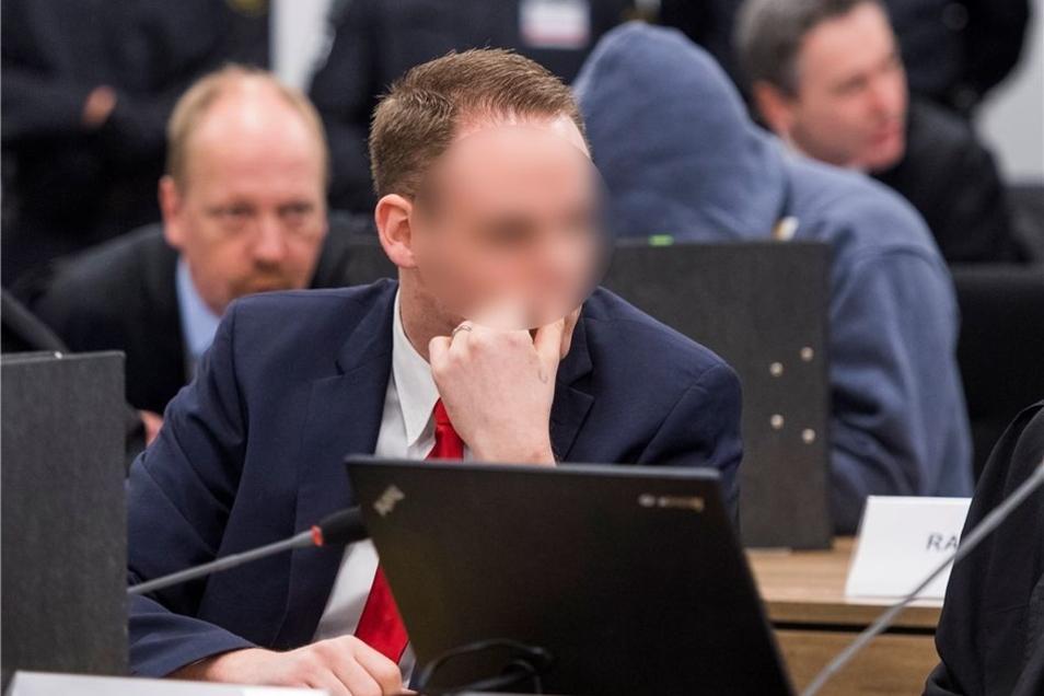 Der Angeklagte Timo S., hinter ihm sitzt der Mitangeklagte Mike S., der sein Gesicht mit einem Kapuzenpulli verdeckt.