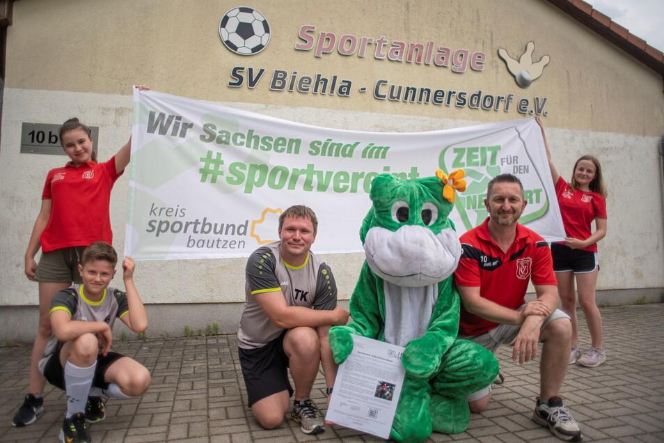 Thomas Kirschner (l.) und Rick Stelzner vom SV Biehla-Cunnersdorf freuen sich mit dem Frosch auf den Froschlauf. Auch Lenny, Clara und Jule helfen wie viele andere Mitglieder mit beim Lauf-Event.