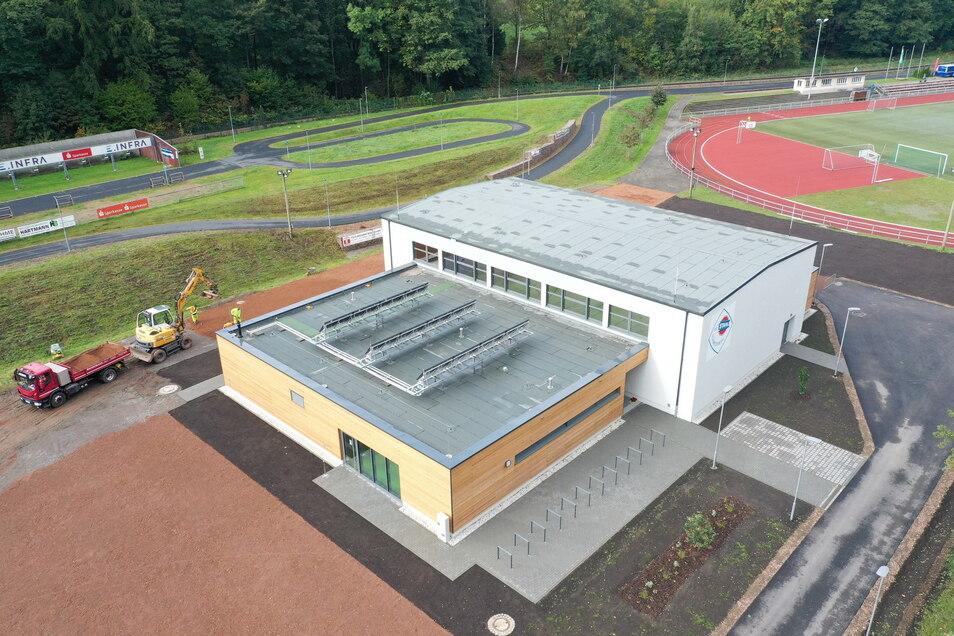 Aus der Vogelperspektive zeigt die Kamera schön, wie sich die Turnhalle in die Anlagen des Gießerei-Sportparks in Schmiedeberg einfügt.