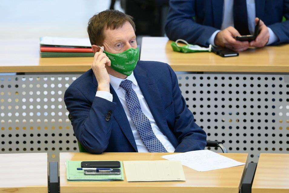 Michael Kretschmer sitzt während der Debatte im Plenum mit Maske auf seinem Platz im Landtag.