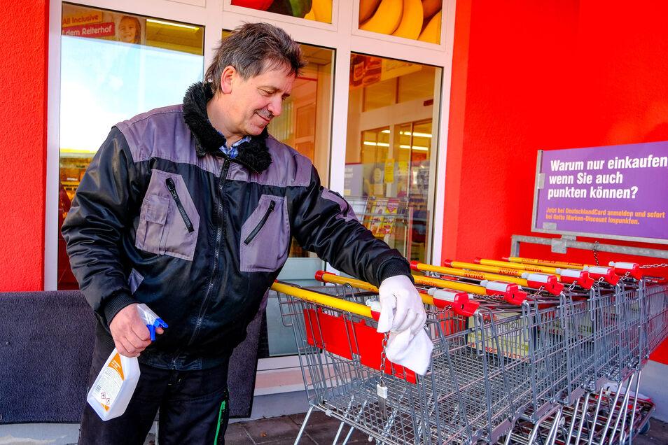 René Friese beim Desinfizieren der Einkaufswagen am Netto - Supermarkt in Radebeul.