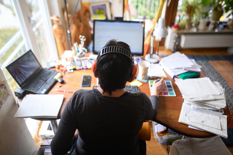 Eine Frau arbeitet mit Hörschutz im Homeoffice. Um die Ausbreitung des Coronaviruses zu verlangsamen, arbeiten viele Arbeitnehmer und Arbeitnehmerinnen von zu Hause aus.