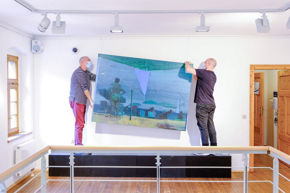 Der Aufbau für die neue Ausstellung ist im vollen Gange. Künstler Christian Manss (r.) hängt mit Stadtgalerist Alexander Lange eines seiner Bilder auf.