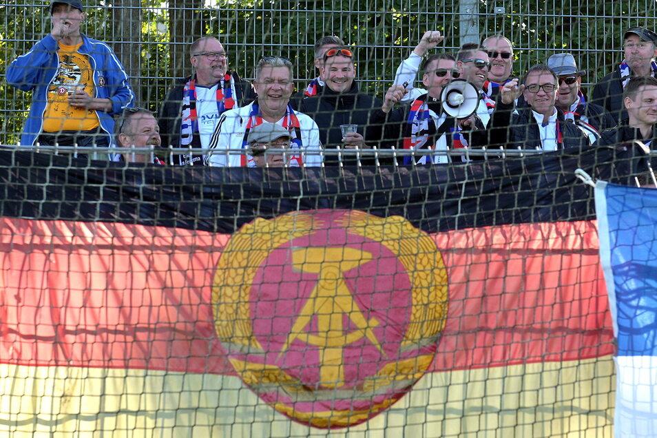 Mit der Fahne der untergegangenen DDR unterstützen Fans eine Auswahl ehemaliger Fußballer in Emden, doch Ostfriesland ist stärker.