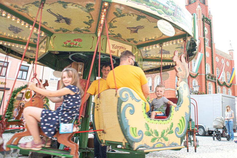 Auch auf dem Marktplatz drehte sich ein historisches Kinderkarussell. Clara, Ludwig und Benjamin Schiller fahren hier gerade damit. Foto: Rene Plaul