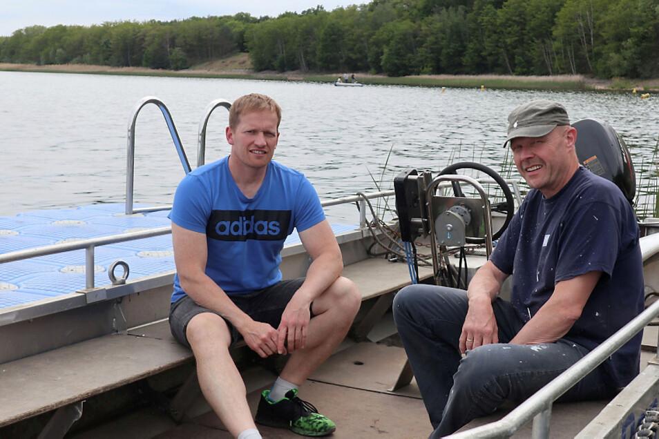 """Marcel Fechner (links), der Leiter der Kanu-Kids Lohsa, und Uwe Schneider, der Vorsitzende des Wassersportvereins """"Am Blauen Wunder"""" Dresden, verweilen unweit der künftigen Regatta-Strecke auf dem Dreiweiberner See."""