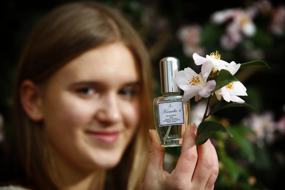 """Franziska Neumann zeigt einen Testflakon des Parfüms, das aus der Duftkamelie """"Minato no akebono"""" gewonnen wurde."""
