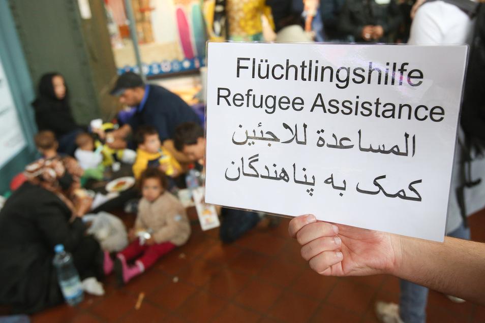Ein freiwilliger Helfer hält im Hamburger Hauptbahnhof ein Schild auf deutsch, englisch und arabisch, auf der Hilfe für Flüchtlinge angeboten wird.