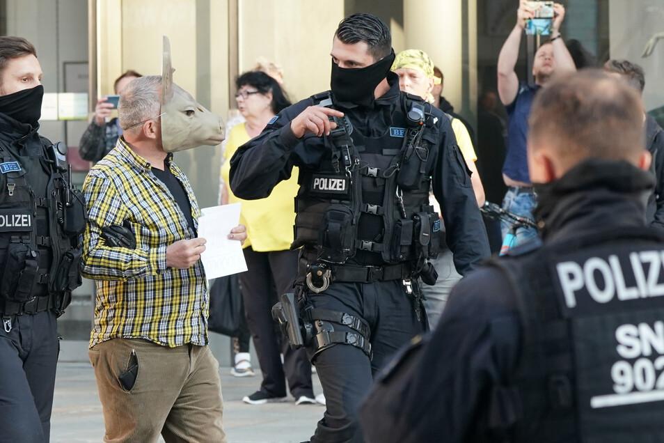 Ein Mann mit einer Maske wird am Freitag in Chemnitz von Polizisten zur Personalienfeststellung mitgenommen. Mitglieder der rechtsextremen Vereinigung Pro Chemnitz hatten eine Kundgebung am Karl-Marx-Monument geplant.
