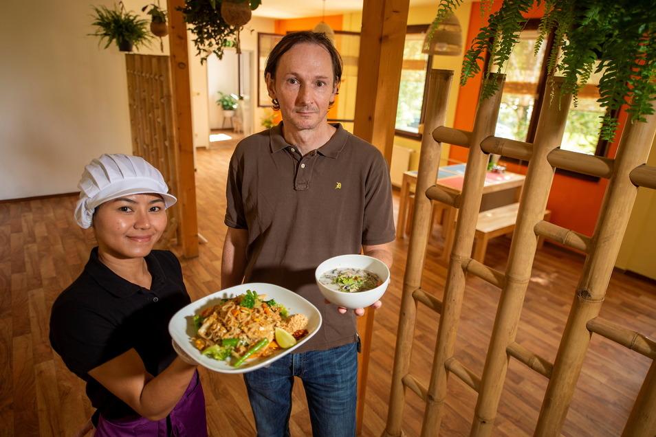 Ratchanee Kotte und ihr Ehemann Oliver Kotte präsentieren zur Eröffnung des Baan Thai Bistros in Pirna eine Curry-Suppe Tom Kha Gai (r.) und gebratene Reisbandnudeln nach Thai Art.