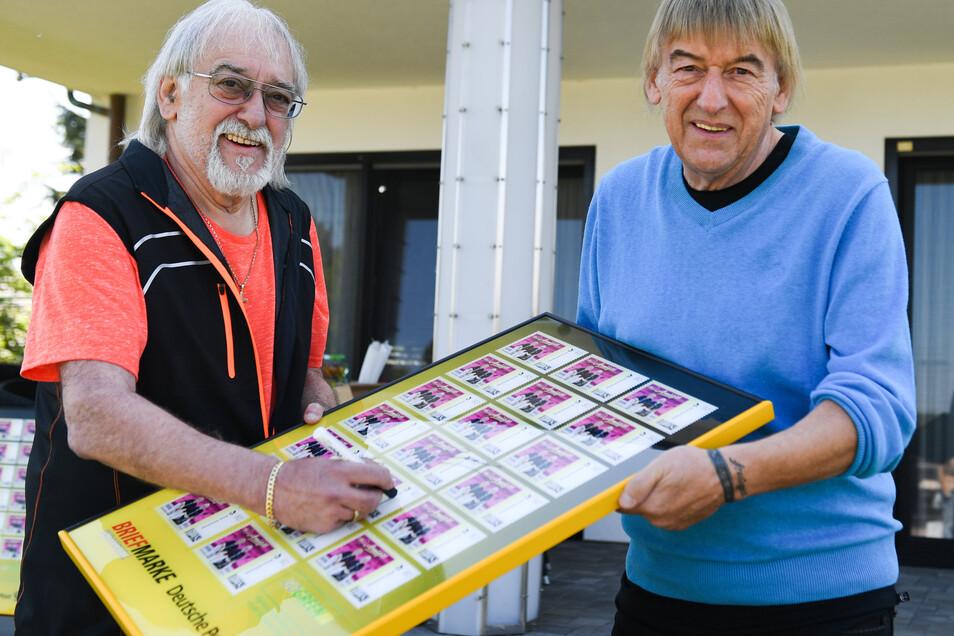 """Die Brüder Bernd (r) und Karl-Heinz Ulrich, """"Die Amigos"""", präsentieren einen Bilderrahmen, der übergroße Exemplare der ihnen gewidmete Briefmarken zeigt."""