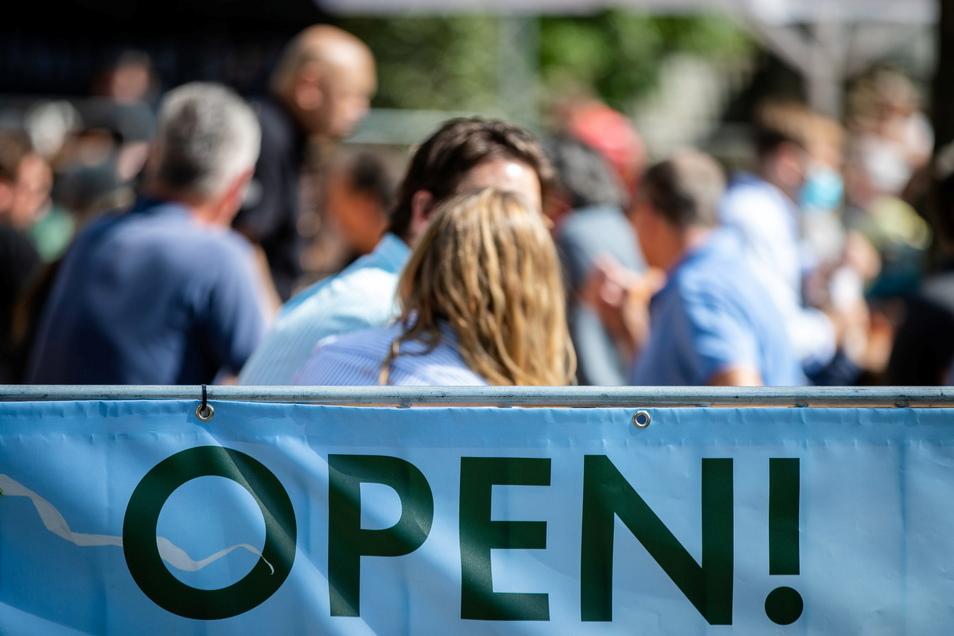 Open - steht auf einem Banner an einem Biergarten geschrieben, in dem Gäste das schöne Wetter genießen. Wenn die Inzidenzen so bleiben, kann die Innengastronomie im Landkreis Meißen am Donnerstag öffnen.