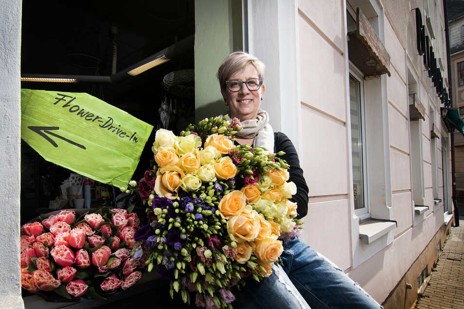 Nur für den Fotografen hat sich Ramona Holstein, Inhaberin des Blumen ABC, außen auf das Fensterbrett ihres Ladens gesetzt. Normalerweise steht sie im Laden und bedient die Kunden in einer Art Drive-In durch das Fenster.