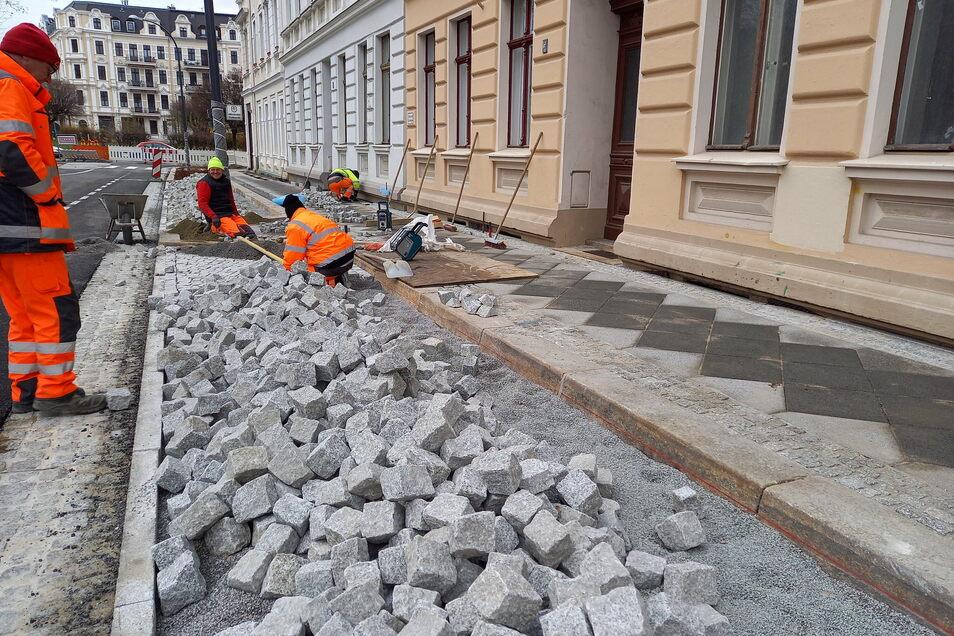 Arbeiter haben bei großer Kälte die Parkflächen mit Granit gepflastert.