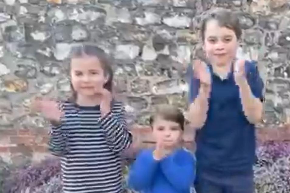 Dieses Bild aus dem Twitter-Feed des Kensington-Palastes zeigt, wie sich die Prinzen George (r), Louis (M) und Prinzessin Charlotte an einem nationalen Applaus für den NHS (das staatliche Gesundheitssystem in Großbritannien und Nordirland) beteiligen, um