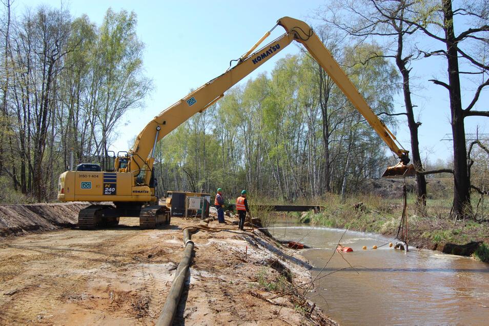 Bevor der Fluss verbreitert wird, entfernt man den Schlamm vom Grund. Die Sohle wird während der Arbeiten mit einer Kiesschicht versehen.