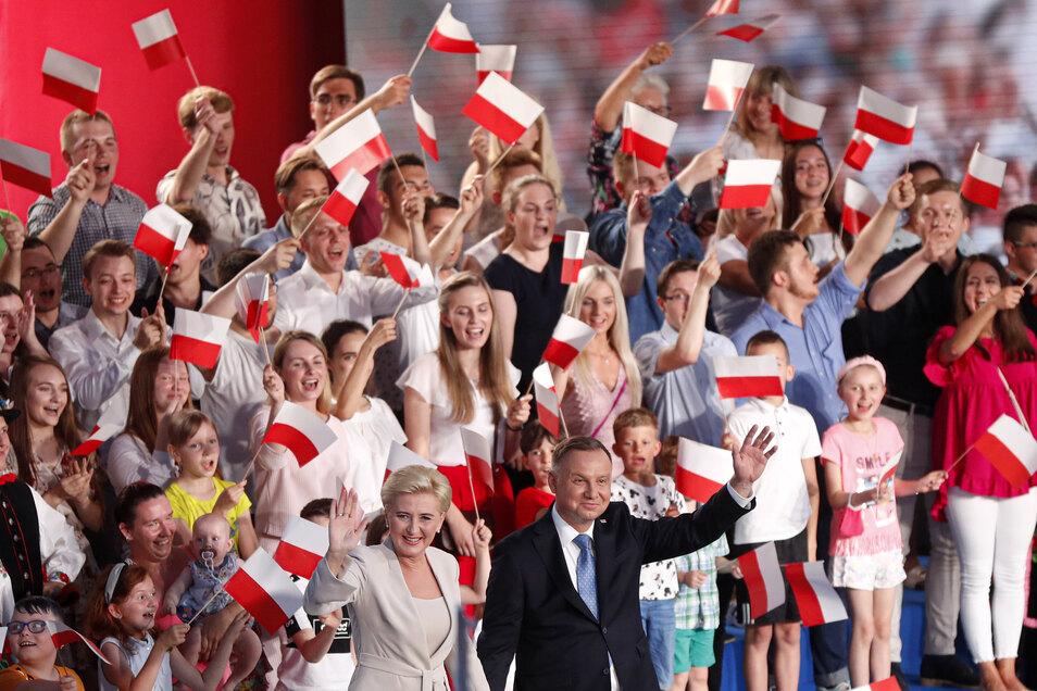 Andrzej Duda (vorne,r), Präsident von Polen, und seine Frau Agata Kornhauser-Duda winken kurz nach dem Ende des Wahltages zur Präsidentschaft ihren Fans zu.
