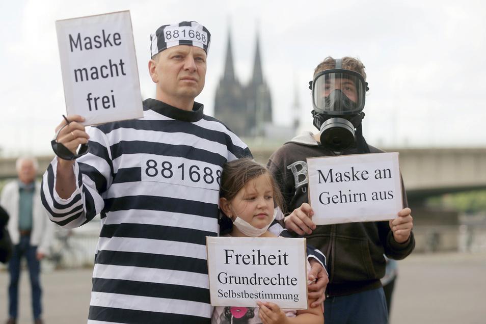 Bei einer Demonstration gegen Corona-Beschränkungen am 23. Mai in Köln hält ein Demonstrant in gestreifter Kleidung, die der Uniform eines KZ-Häftlings nachempfunden ist sein umstrittenes Plakat hoch.