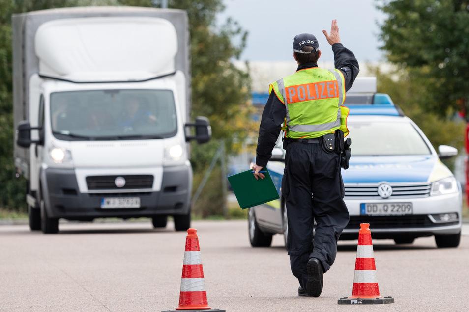Ein Polizist winkt am Rastplatz Dresdner Tor an der A4 einen Transporter zur Kontrolle raus.