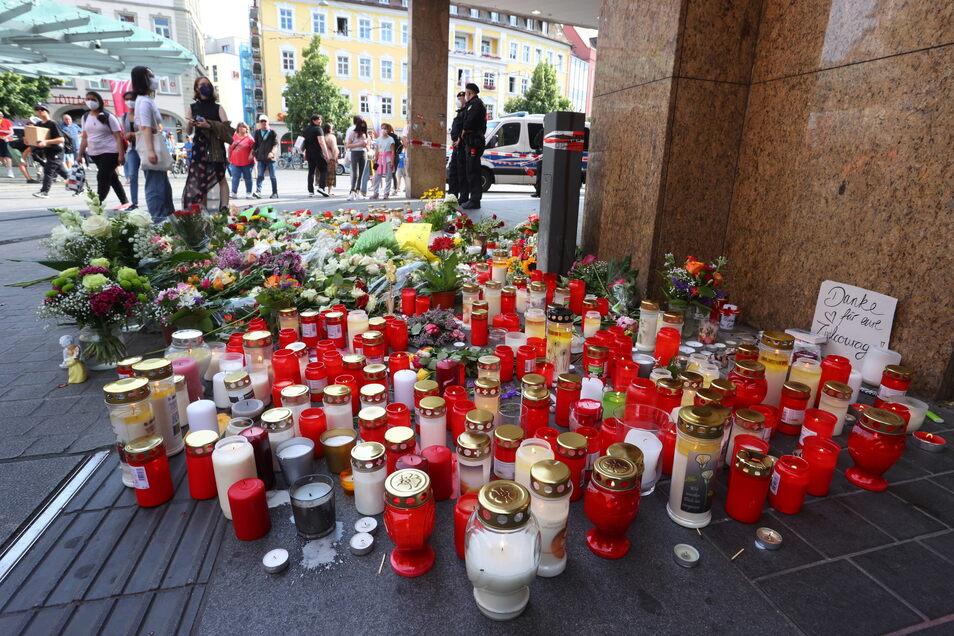 Blumen und Kerzen stehen vor dem geschlossenen Woolworth-Kaufhaus in der Innenstadt von Würzburg. HIer hatte ein Mann am Freitag wahllos Menschen mit einem Messer angegriffen.