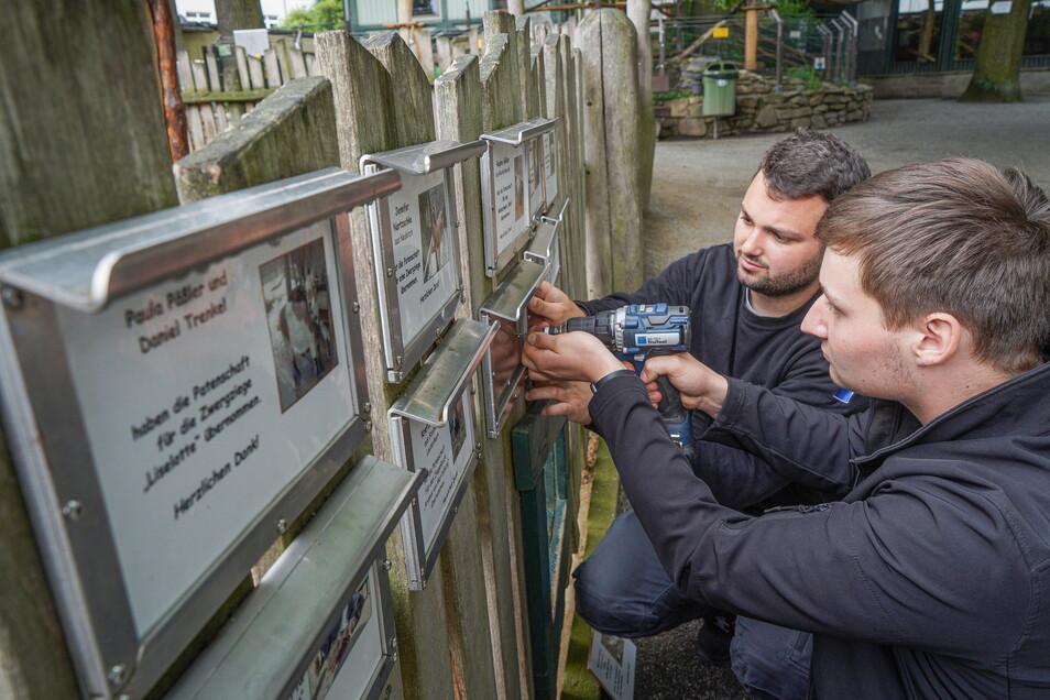 Markus Bolzmann (l.) und Moritz Feurich - beides Lehrlinge bei Trumpf in Neukirch - montieren im Tierpark Bischofswerda neue Schilderträger für die Infos über Tierpatenschaften.