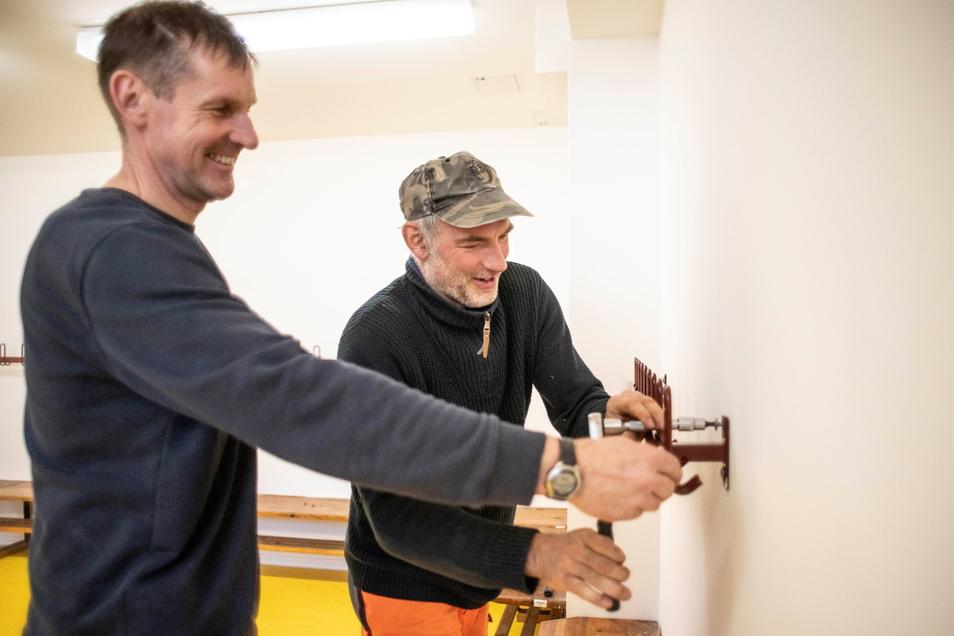 Heiko Morche (l.) und René Schaaf vom Bauhof bringen bringen Kleiderhaken im Umkleideraum an.
