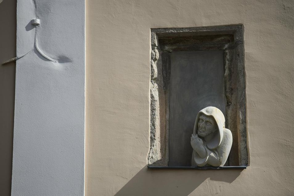 """Der Mönchskopf hat seinen Platz in einer Nische der Fassade der Görlitz-Information am Obermarkt/Ecke Fleischerstraße gefunden. Er blickt hinüber zur """"Suchenden Mutter"""" an der Fassade der Fleischerstraße 2."""