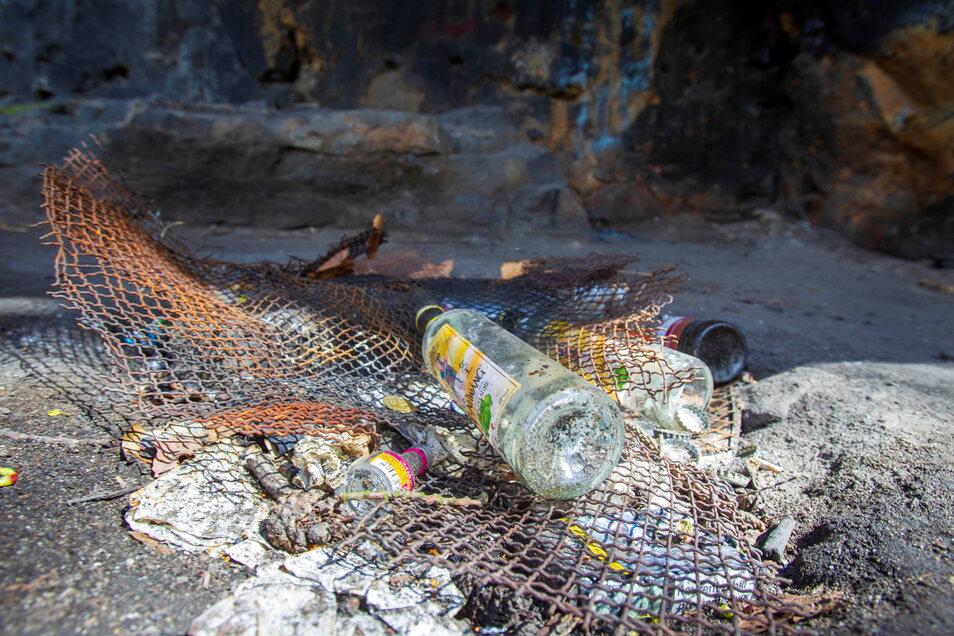 Unbekannte haben eine Feuerstelle an dem Aussichtspunkt Wettinhöhe bei Pirna angelegt. Auch Flaschen liegen herum.