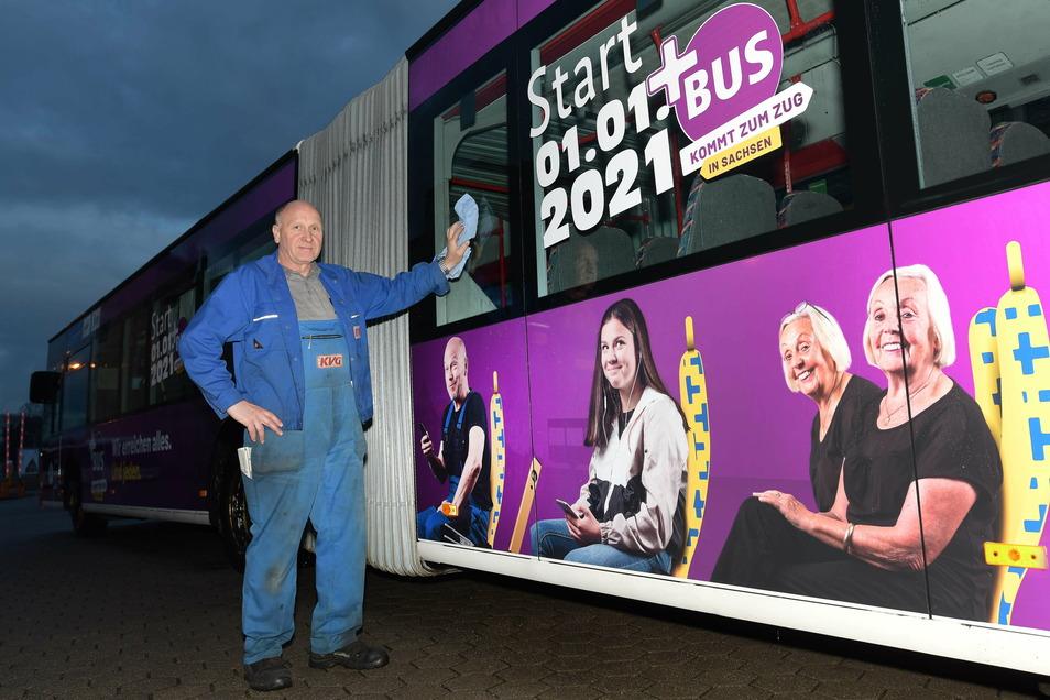 An zwei Bussen ist es groß zu sehen: Der neue Fahrplan kommt. Mitarbeiter Michael Stephan sorgt für frischen Glanz.