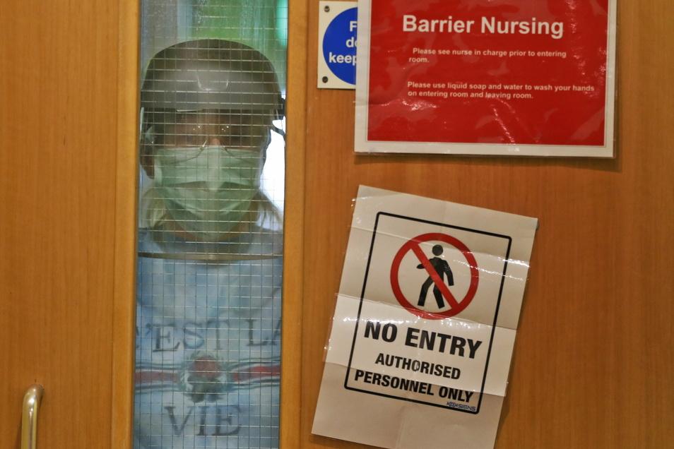 Eine Krankenschwester mit Mundschutz blickt durch das Fenster einer geschlossenen Tür eines Pflegeheims in Nottingham.