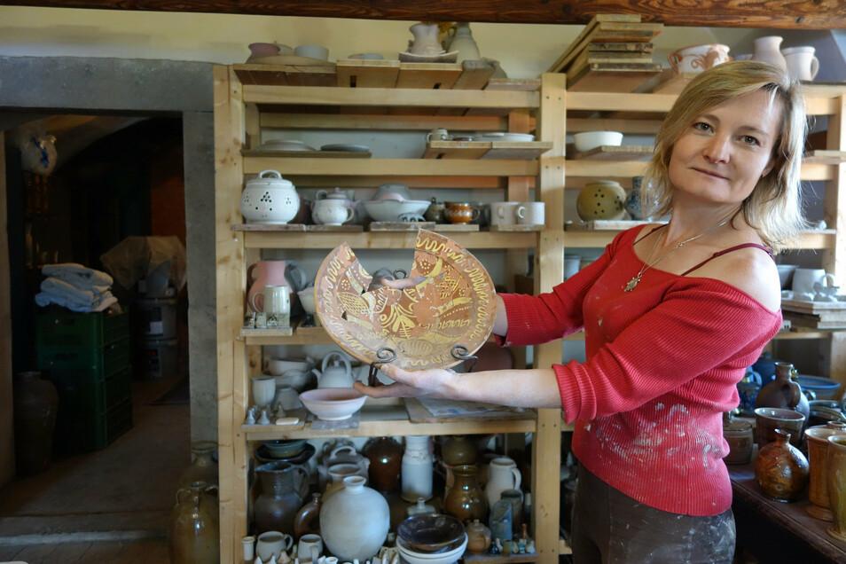 Magdalena Brožová zeigt einen in Engobe-Keramik gefertigten historischen Teller aus Lewiner Geschirr. Die Keramikerin hat die jahrhundertelange Tradition neu belebt.