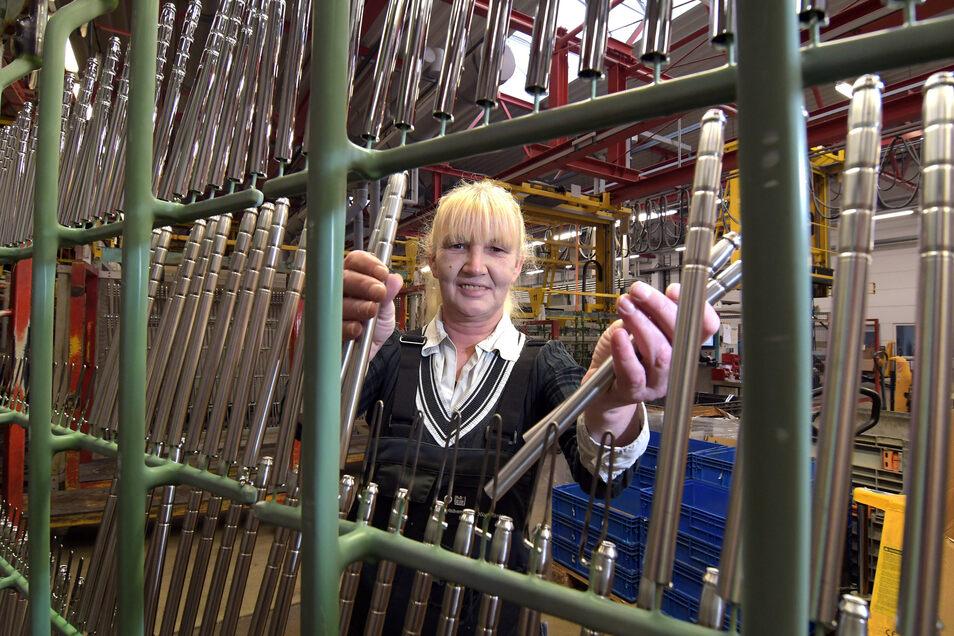 Mitarbeiterin Gabriele Grimpe steckt bei der Firma Metallveredlung Teile für Kopfstützen auf Teileträger.